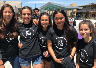 A group of female students wearing Let's Be Kind black T-shirts