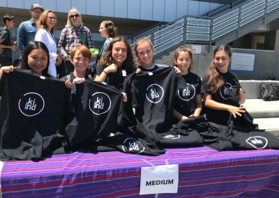 A group of female students holding up black Let's Be Kind T-shirts at a booth on campus