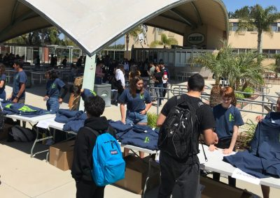 A crowd of students around tables with Let's Be Kind branded T-shirts